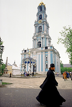 Monk and bell tower of Trinity Lavra of St Sergius, Russian Orthodox monastery at Sergiyev Posad, Zagorsk, near Moscow, Russia