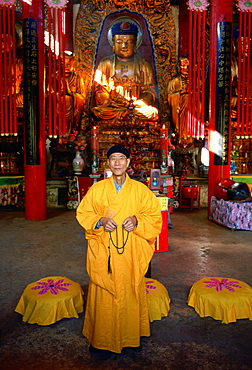 A Buddhist monk in saffron coloured robes praying in front of a statue of Buddha at the Buddhist Temple in Huating, China