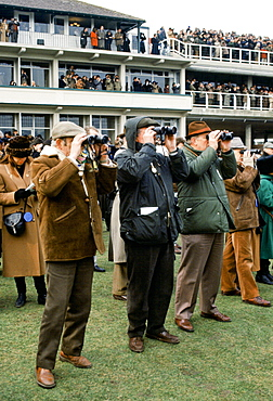 Spectactors with binoculars in front of grandstand at Cheltenham Racecourse for the National Hunt Festival of Racing, UK