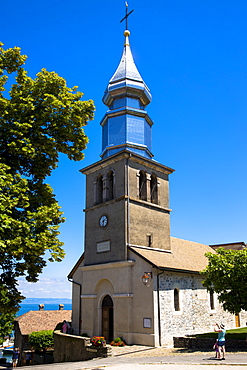 Tourist photographs Saint Pancrace d'Yvoire church in the old district of Yvoire by Lac Leman (Lake Geneva), Rhone-Alpes, France, Europe