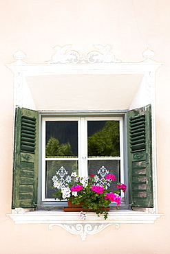Window in old painted stone 17th century building in the Engadine Valley in the village of Guarda, Graubunden, Switzerland, Europe