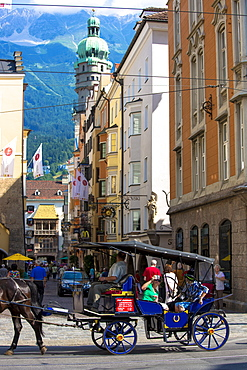 Tourists view Goldenes Dachl (Golden Roof) from horse-drawn carriage by Herzog Friedrich Strasse, Innsbruck the Tyrol, Austria, Europe