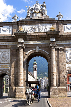 Tourists in horse-drawn carriage pass Triumphal Arch and Spitalskirche in Innsbruck, the Tyrol, Austria, Europe