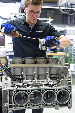 Engineer applying lubricating oil to piston for 6.3 litre V8 engine, Mercedes-AMG engine production factory in Affalterbach, Bavaria, Germany, Europe