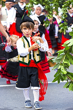 Spanish boy playing musical instrument at traditional fiesta at Villaviciosa in Asturias, Northern Spain, Europe
