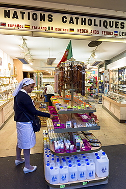 Religious icons, holy water and statues on sale at souvenir shops at pilgrimage location of Lourdes, Pyrenees, France, Europe