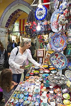 Western woman tourist buying hand-painted ceramics in The Grand Bazaar (Great Bazaar) (Kapali Carsi),  Beyazi, Istanbul, Turkey, Europe