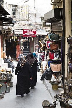 Muslim women wearing traditional robes and veils shopping in The Grand Bazaar (Great Bazaar) (Kapali Carsi), Beyazi, Istanbul, Turkey, Europe