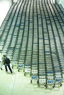 Generic shot of traveller collecting a trolley from hundreds of luggage trolleys at an airport, United Kingdom, Europe