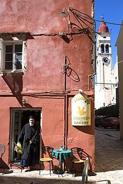 Greek Orthodox priest in traditional robes buying bread from bakery shop in Kerkyra, Corfu Town, Corfu, Greek Islands, Greece, Europe