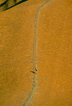 Tourist visiting Ayers Rock in Australia holds onto the roped handrail for support