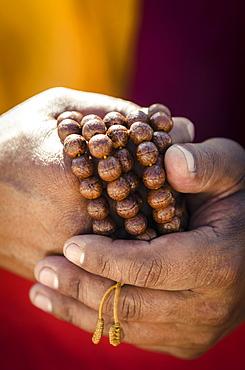 A Buddhist monk holds prayer beads (Japa Mala), Bodhnath, Nepal, Asia