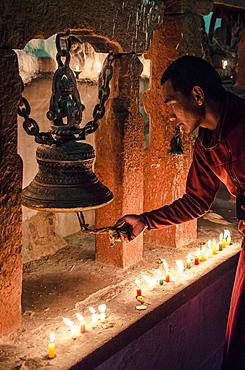 A Buddhist monk rings a prayer bell during the full moon celebrations, Bodhnath stupa, Bodhnath, Nepal, Asia