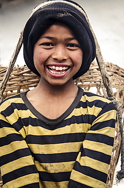 A boy carrying a doko (head basket), Tolka, Annapurna Conservation Area, Nepal, Asia