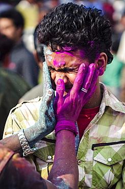 Two men exchange coloured powder during Holi festival celebrations, Basantapur Durbar Square, Kathmandu, Nepal, Asia