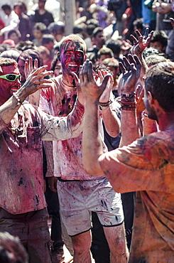 Westerners covered in coloured powder during Holi festival celebrations, Basantapur Durbar Square, Kathmandu, Nepal, Asia