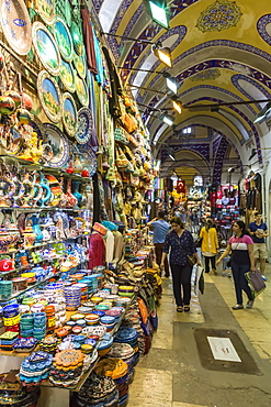 Shoppers with bags on a Friday afternoon in street with decorated ceiling and pottery stall, Grand Bazaar, Istanbul, Turkey, Europe