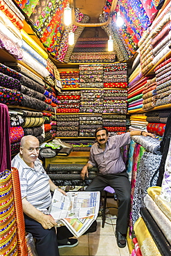 Sellers (vendors) of traditional Turkish fabrics seated in their shop reading a newspaper, Grand Bazaar, Istanbul, Turkey, Europe