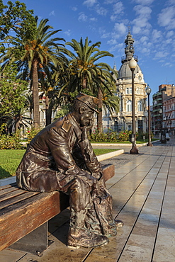 Bronze statue of a sailor on a wooden bench with palm trees, Town Hall backdrop, Cartagena, Murcia Region, Spain, Europe