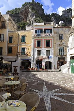 Town square with restaurant tables and colourful buildings, star shaped paving, Atrani, near Amalfi, Costiera Amalfitana (Amalfi Coast), UNESCO World Heritage Site, Campania, Italy, Europe