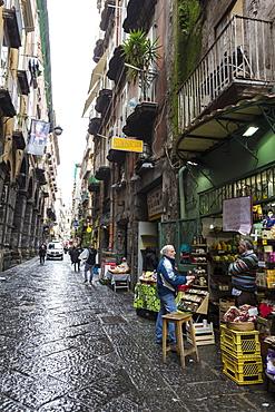 Shopkeeper and customer in wet narrow street, Historic Centre (Centro Storico), UNESCO World Heritage Site, Naples, Campania, Italy, Europe
