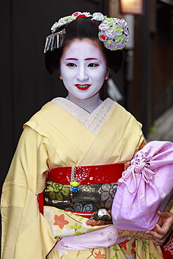 Smiling maiko, apprentice geisha, with yellow robes, stops in street on way to evening appointment, Gion, Kyoto, Japan, Asia