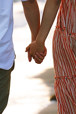 Close up of a couple holding hands by the beach