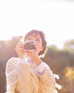 Portrait of a Japanese woman in a white cardigan holding an old camera