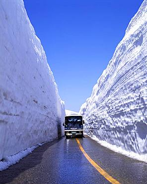 Bus on snow-banked road, Toyama, Japan