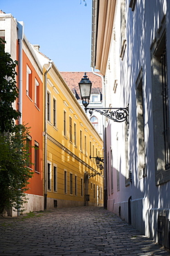 An empty cobbled alleyway with colourful houses in the Castle Quarter, Budapest, Hungary