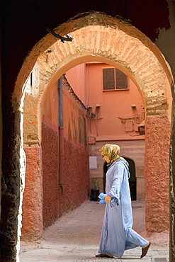 A Moroccan woman in front of an archway in the alleys of Marrakesh, Morocco