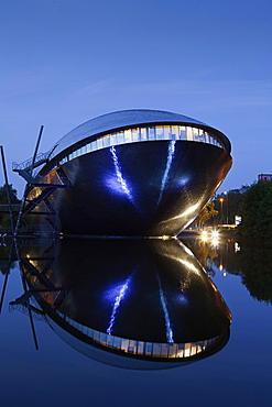 Symmetrical reflection of Atlantic Hotel Universum at night, Bremen, Germany