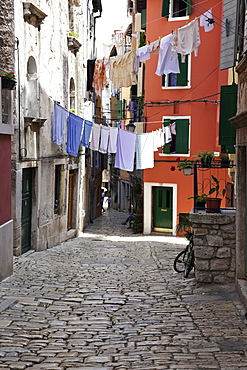 Street with clothes on cable line at Rovinj, Croatia