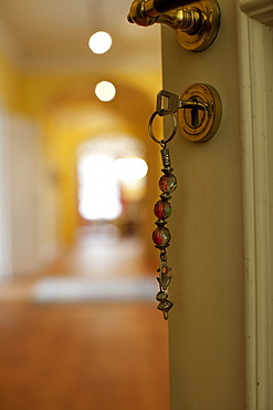 Close-up of door's keyhole with key hanging in lock