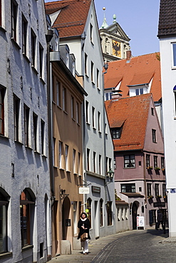 Woman walking in alley at Pfladergasse, Augsburg, Bavaria, Germany