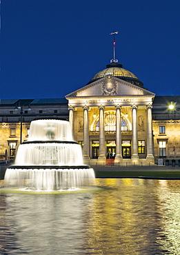 Facade of illuminated Kurhaus and fountain at Wiesbaden, Hesse, Germany