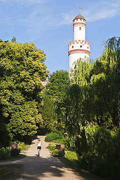 Rear view of women jogging in Castle Park in front of White Tower, Bad Homburg, Germany