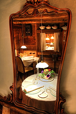 Reflection in mirror of set table at Restaurant La Stua de Michil, South Tyrol, Italy