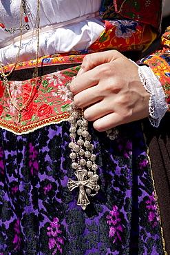 Close-up of woman holding rosary at Cagliari's Sant 'Efisio, Sardinia, Italy