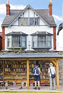 Men at outside bookstore in Hay-on-Wye village, Powys, Wales, UK