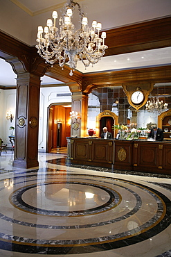 Receptionist standing at reception counter in hotel, Italy