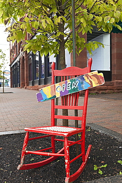 Red rocking chair with board open on it at pavement, Nova Scotia, Canada