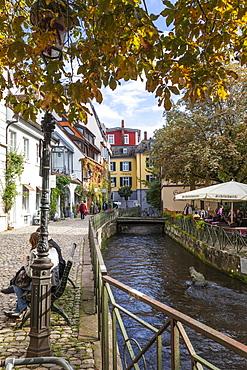 People sitting beside Gerberau cannel in old town, Freiburg, Germany