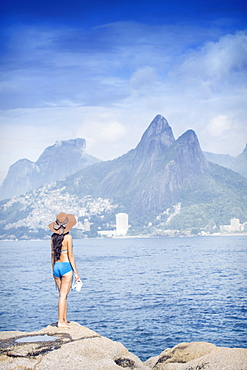 A 20-25 year old young Brazilian woman standing on the Arpoador rocks with Ipanema and the Morro Dois Irmaos hills in the distance, Rio de Janeiro, Brazil, South America