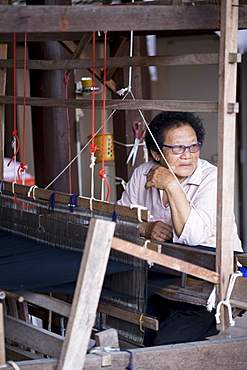 Tai Lue (Lu) indigenous weaver at a wooden loom weaving Tai Lue traditional clothing, Chiang Mai, Thailand, Southeast Asia, Asia