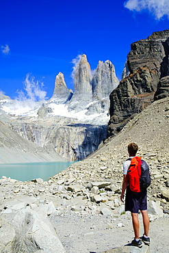 Hiker in front of the rock towers that give the Torres del Paine range its name, Torres del Paine National Park, Patagonia, Chile, South America