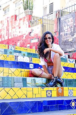 Young Brazilian woman in sunglasses sitting on the Selaron steps in Lapa, Rio de Janeiro, Brazil, South America
