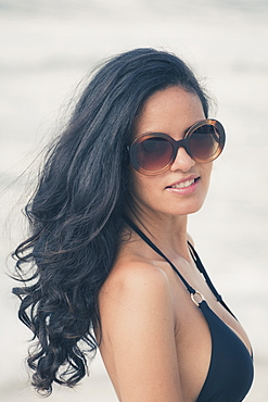 Young Brazilian (Latin American) (Latina) woman on the beach in a bikini and sunglasses, Rio de Janeiro, Brazil, South America