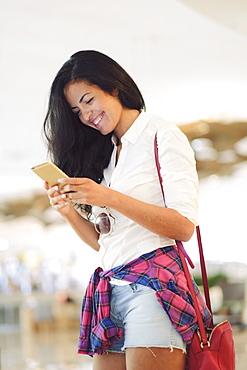 Young Brazilian woman using her mobile phone in central  Rio de Janeiro, Brazil, South America