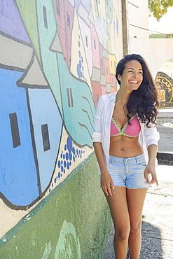 Young Brazilian woman happy and smiling next to a graffiti wall in Lapa, central Rio de Janeiro, Brazil, South America